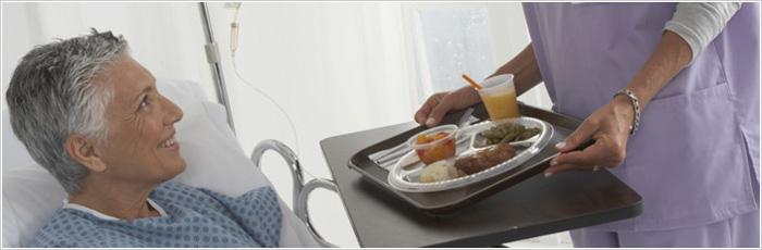 Patient In Hospital Bed Receiving Breakfast From Nurse